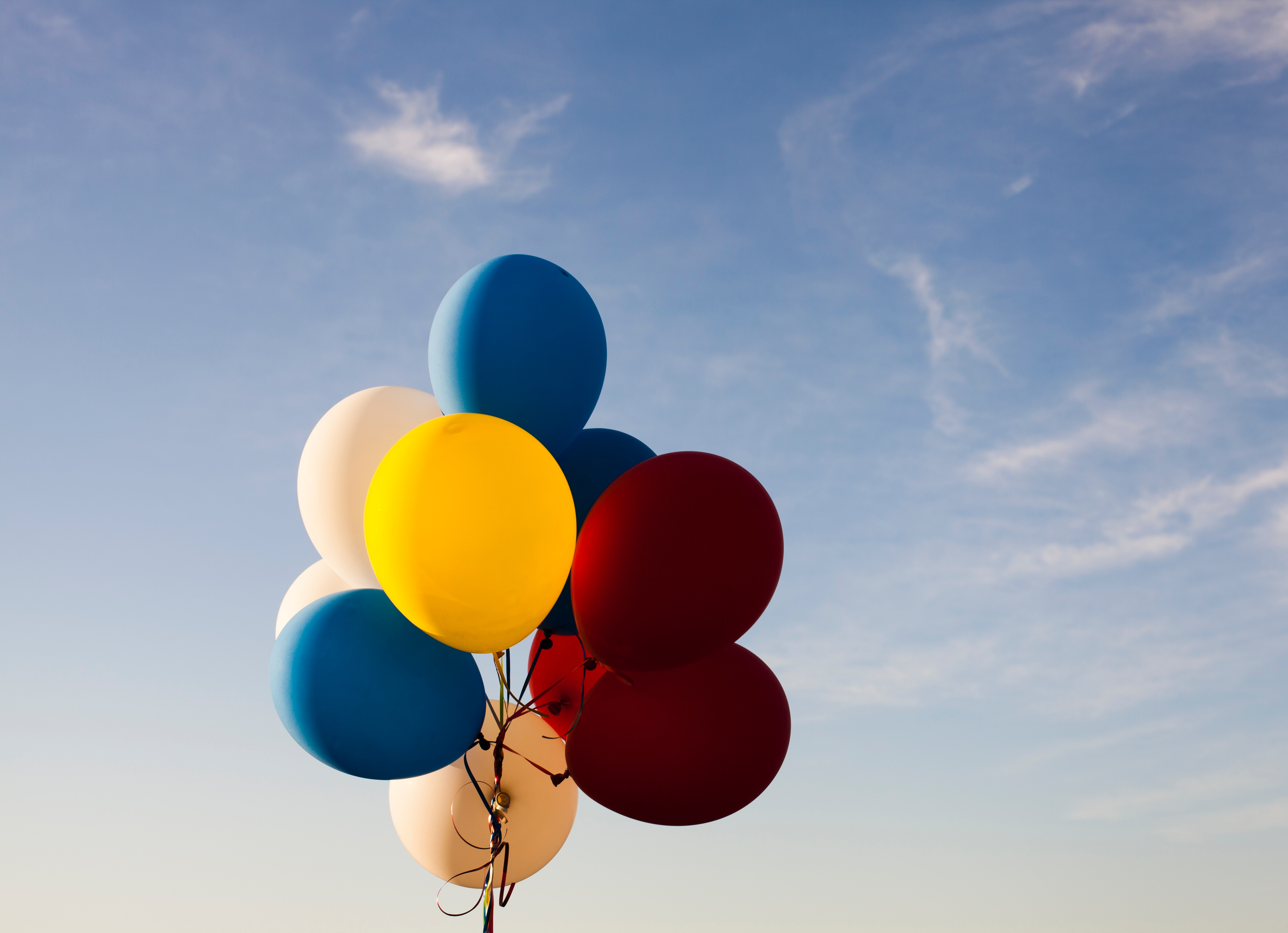 A bunch of balloons against a blue sky.