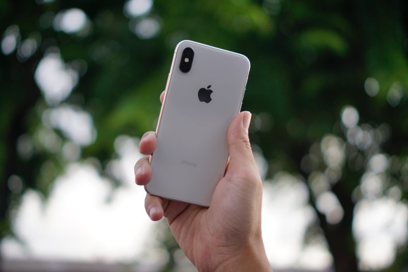 A hand holding an iPhone with a backdrop of trees.