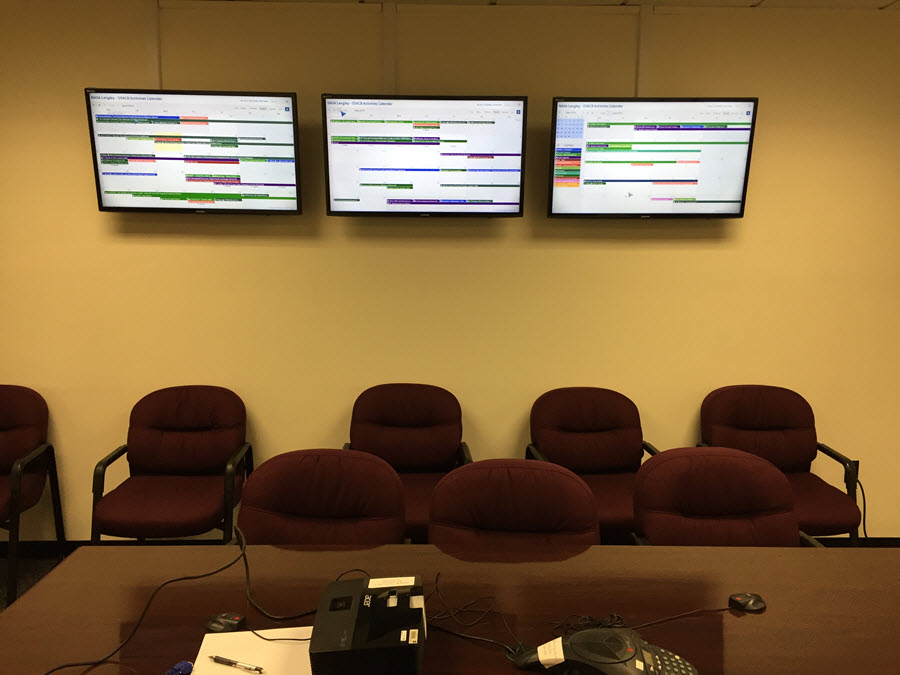 A photo showing three tv displays of a customized Teamup calendar.